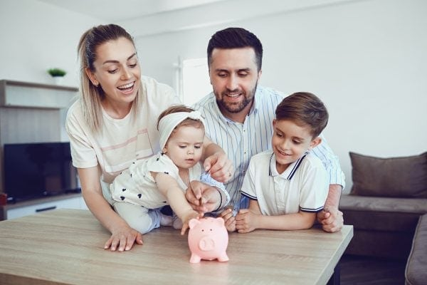 Mom and dad teaching children simple money-saving tips with a pink piggy bank.