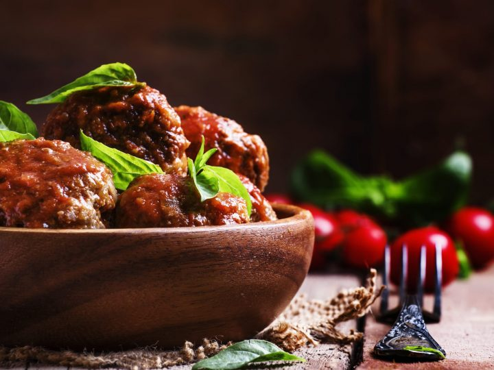 sweet and sour meatballs in a bowl with herbs