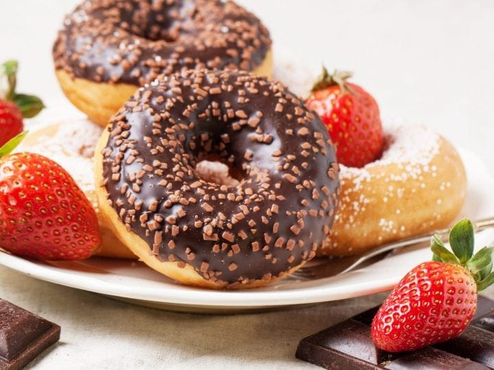 chocolate glazed donuts with sprinkles and strawberries on a plate