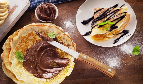 crepes on a plate and a stack of crepes with nutella.