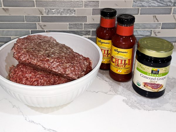 raw hamburger meat served in white bowl, ingredients with chili sauce and concord grape jelly