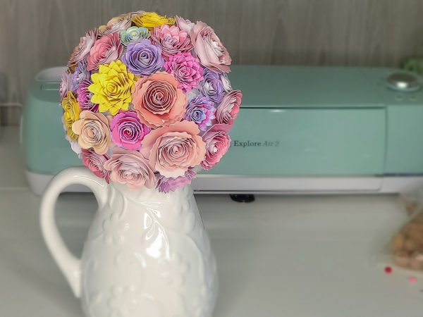 paper flower bouquet in a vase on a dreambxo craft table next to a cricut explore air 2 machine