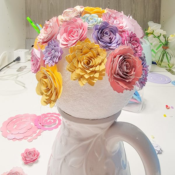 in-progress photo of a home decor diy - paper flowers being glued to a ball to make a bouquet