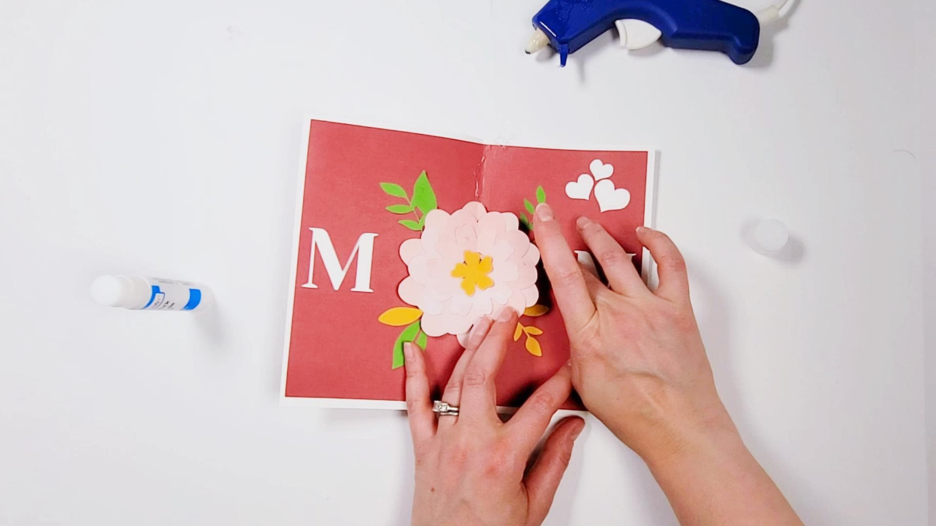 image of person adding leaves cut with a cricut machine to a pop up mother's day card