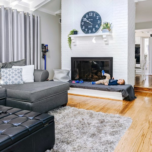 living room with white brick fireplace and black matte trim that used to be a brass fireplace trime before it was painted