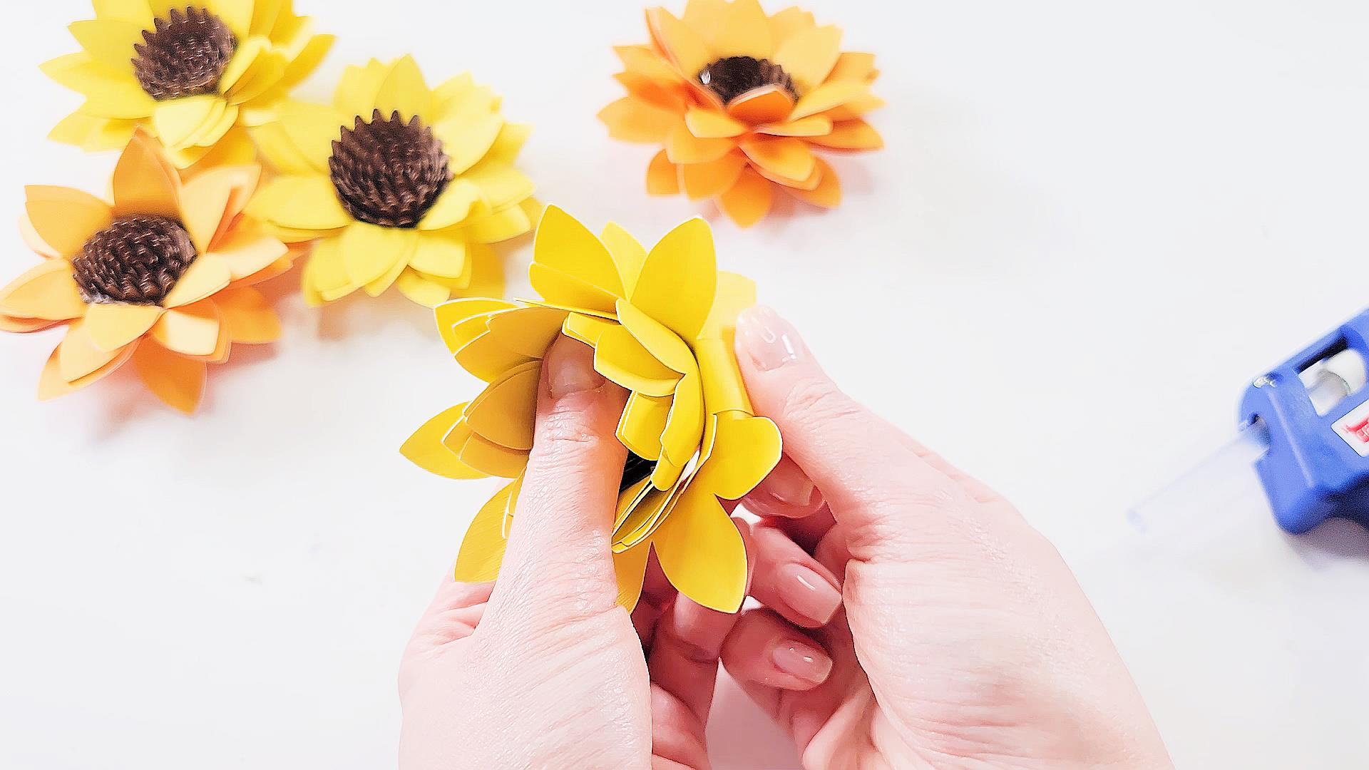 folding petals back on a nearly complete sunflower paper flower