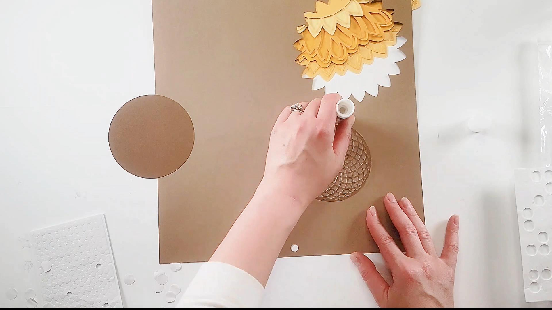 using a glue stick on the last layer of our sunflower mandala