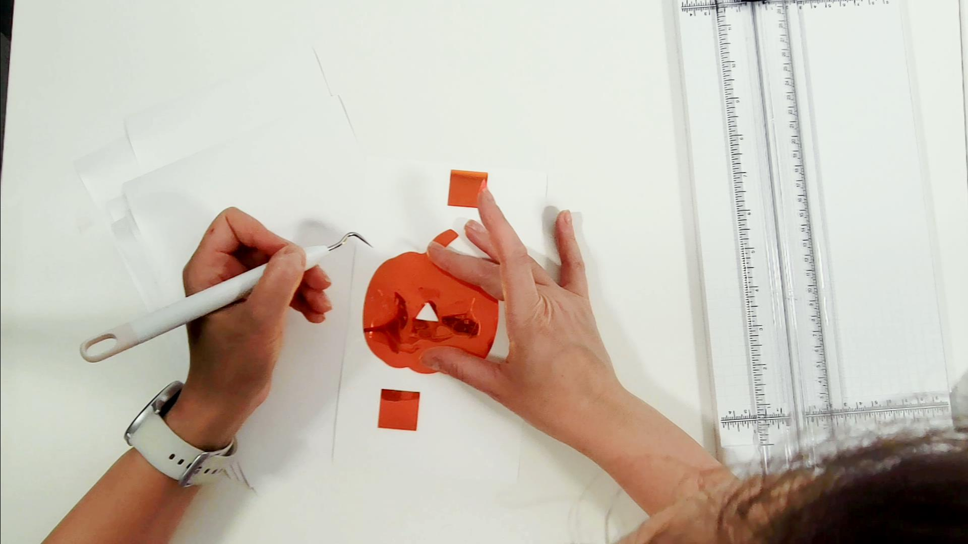 weeding the pumpkin shape from orange vinyl for a welcome sign